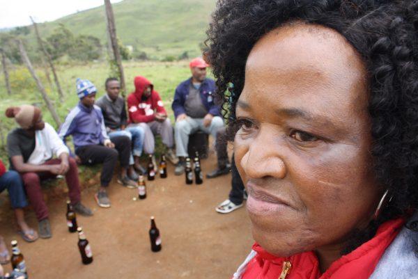 Veteran HIV counselor Gethwana Mahlase speaks to men outside a tavern in Vulindlela.