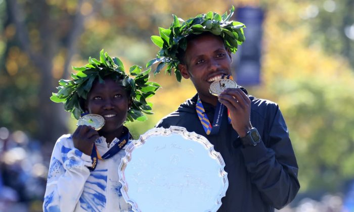 Women's winner Mary Keitany of Kenya and Men's winner Lelisa Desisa of Ethiopia pose with their medals at the finish line during the 2018 TCS New York City Marathon on Nov. 4, 2018 in Central Park in New York City.(Elsa/Getty Images)