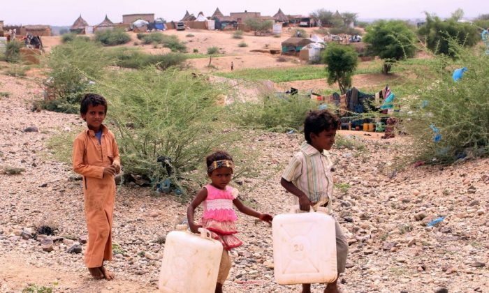 Displaced Yemeni children from Hodeida carry water containers as they walk to a nearby well to fill them in the northern district of Hajjah province, on October 22, 2018. (ESSA AHMED/AFP/Getty Images)
