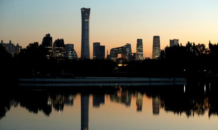 The cityscape of the Beijing Central Business District, or Beijing CBD, is reflected in a pond during sunset on Oct. 17, 2018. (Thomas Peter/Reuters)