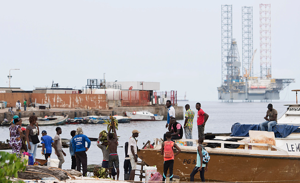 An off-shore oil rig is pictured off the coast of Port-Gentil as people carry goods from a boat to the shore in Gabon on Jan. 19, 2017.   (Photo credit should read JUSTIN TALLIS/AFP/Getty Images)