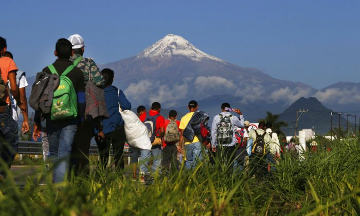 Central American migrants begin their morning trek as part of a caravan of some 4,000 people hoping to reach the United States border, as they face the Pico de Orizaba volcano upon departure from Cordoba, Veracruz state, Mexico, on Nov. 5, 2018. They reached Mexico City by Nov. 6. (AP Photo/Marco Ugarte)