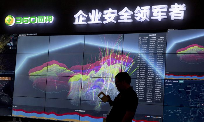 A worker is silhouetted against a computer display showing a live visualization of the online phishing and fraudulent phone calls across China in this file photo. China Telecom is employing a different method of cyber-spying, namely diverting internet traffic. (Ng Han Guan/AP)