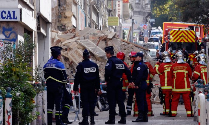 French police and rescue workers are seen near rubble after buildings collapsed in central Marseille, France, on Nov. 5, 2018. (Jean-Paul Pelissier/Reuters)