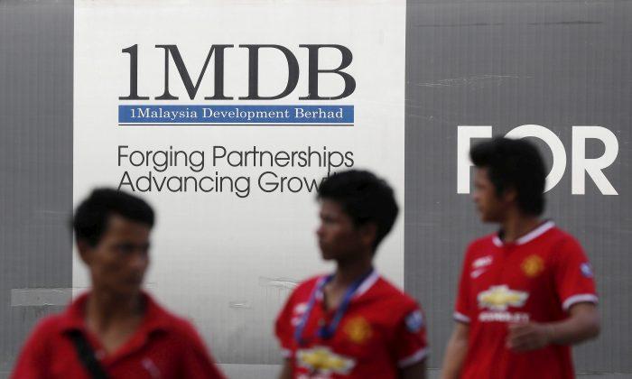 Men walk past a 1 Malaysia Development Berhad (1MDB) billboard at the fund's flagship Tun Razak Exchange development in Kuala Lumpur on March 1, 2015.   (Olivia Harris/File Photo/Reuters)