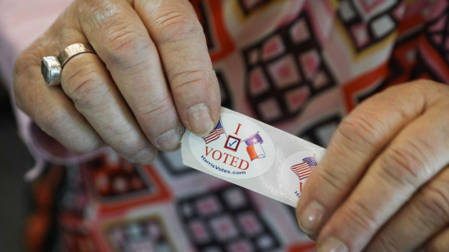 "A voter in Texas hands out ""I voted"" stickers"