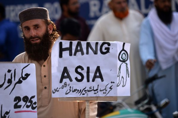 "A supporter of Tehreek-e-Labaik, a hardline religious political party, holds a placard reading ""Hang Asia"""