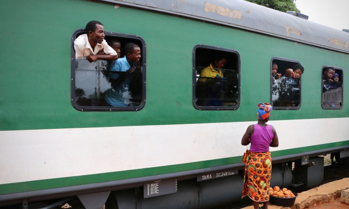 Street and food vendors approach passengers on a train in northern Mozambique on March 10, 2018.   Malawian NGOs and opposition parties are asking why an election kit for the country's elections next year were found on a train in neighboring Mozambique. (Adrien Barbier/AFP/Getty Images)