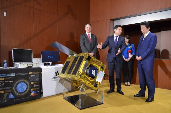 Astroscale CEO Nobu Okada (C) demonstrates a mockup of his company's space debris removal apparatus to Japanese Prime Minister Shinzo Abe.