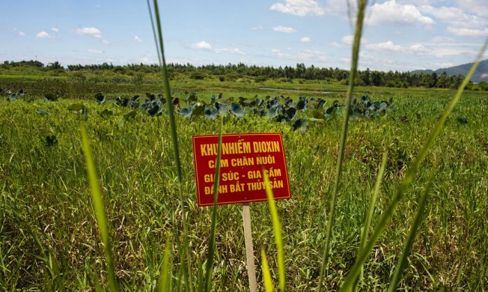 "A warning sign stands in a field contaminated with dioxin near Danang airport, during a ceremony marking the start of a project to clean up dioxin left over from the Vietnam War, at a former U.S. military base in Danang, Vietnam. The sign reads; ""Dioxin contamination zone - livestock, poultry and fishery operations not permitted."" (Maika Elan/AP Photo)"
