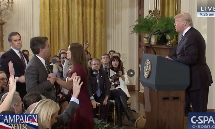 CNN's chief White House correspondent Jim Acosta pushes away the arm of a White House intern after he refuses to hand over the microphone, during a press conference at the White House on Nov. 7, 2018. (C-SPAN)