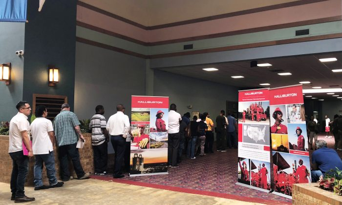 Job seekers line up at a job fair of an oil services giant Halliburton at the MCM Grande Fundome hotel in Odessa, Texas, on July 19, 2018.   (Liz Hampton/Reuters)