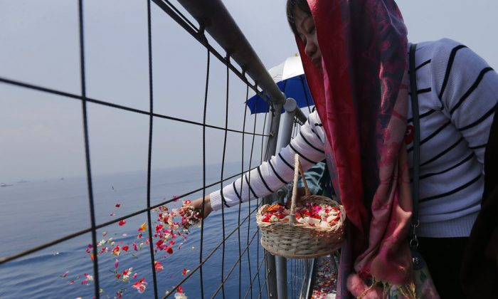 A relative sprinkles flowers for victims in the crashed Lion Air flight 610 aboard an Indonesia Navy ship in the waters where the airplane is believed to have crashed in Tanjung Karawang, Indonesia,Nov. 6, 2018. (AP/Tatan Syuflana)