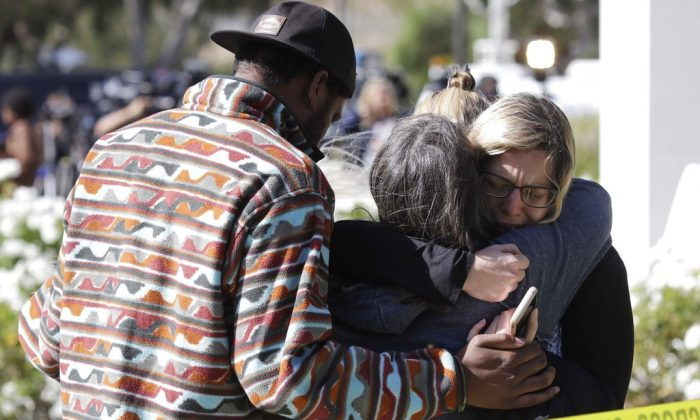 Mourners embrace outside of the Thousand Oaks Teen Center, where relatives and friends gathered in the aftermath of a mass shooting in Thousand Oaks, Calif., on Nov. 8, 2018. (AP Photo/Marcio Jose Sanchez)