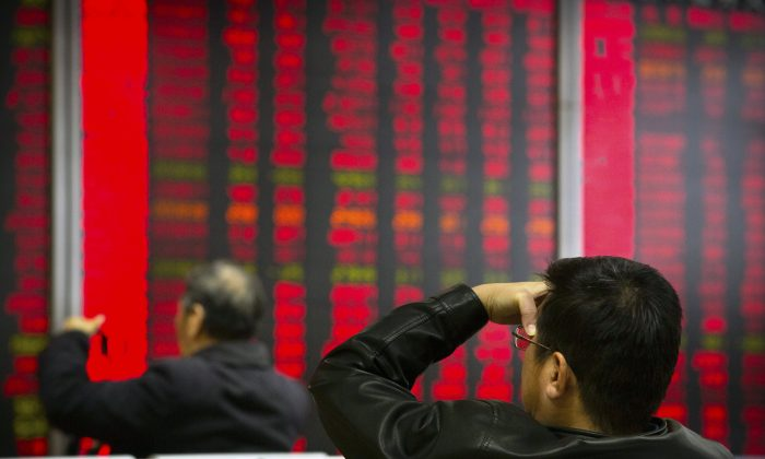 Chinese investors monitor stock prices at a brokerage house in Beijing on Oct., 31, 2018. (Mark Schiefelbein/AP)