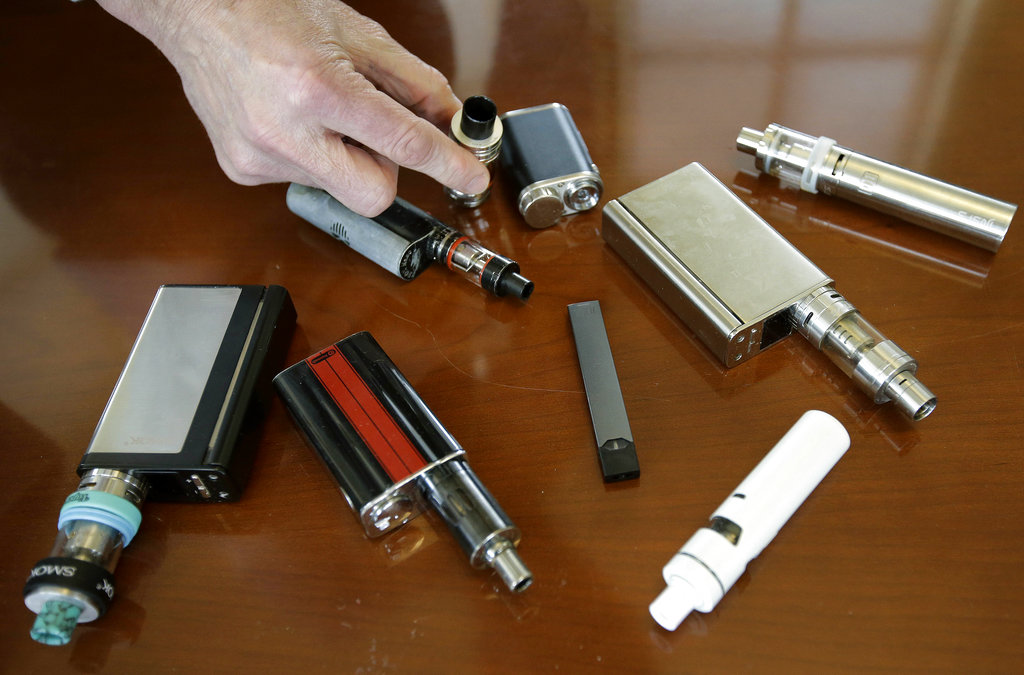 A high school principal displays vaping devices that were confiscated from students