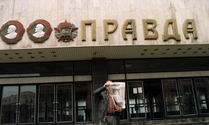 "File photo of a man holding up a copy of ""Pravda"" in front of the entrance of the building of the Soviet newspaper in Moscow on Aug. 28, 1991. (GERARD FOUET/AFP/Getty Images)"