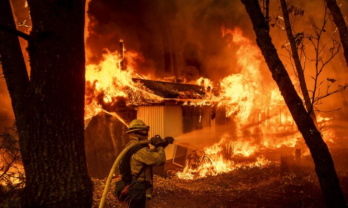 Firefighter Jose Corona sprays water as flames from the Camp Fire consume a home in Magalia, Calif., on Nov. 9, 2018. (AP /Noah Berger)