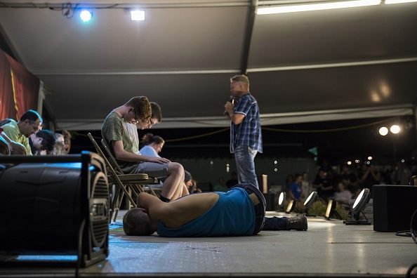 A boy lays on the stage after falling out of his chair while hypnotized during a comedy show at the Montgomery County Agricultural Fair in Gaithersburg, Md., on Aug. 19, 2017. (Samuel Corum/Anadolu Agency/Getty Images)
