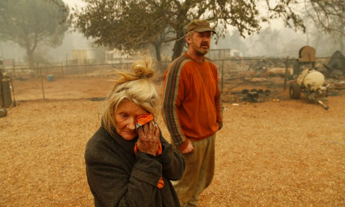 "Cathy Fallon wipes her face beside her son Gabriel Fallon as she stands near the charred remains of her home Friday, Nov. 9, 2018, in Paradise, Calif. ""I'll be darned if I'm gonna let those horses burn in the fire"" said Fallon, who stayed on her property to protect her 14 horses, ""It has to be true love."" All of the horses survived. (John Locher/AP Photo)"