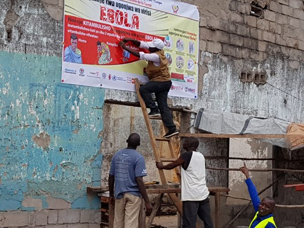 Workers fix Ebola awareness poster
