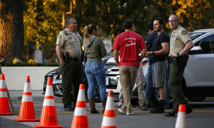 Thousand Oaks residents await to claim their vehicles as FBI agents verify vehicle registrations of autos parked in the lot of the Borderline Bar & Grill bar in Thousand Oaks, Calif., on Nov. 9, 2018. (AP Photo/Damian Dovarganes)