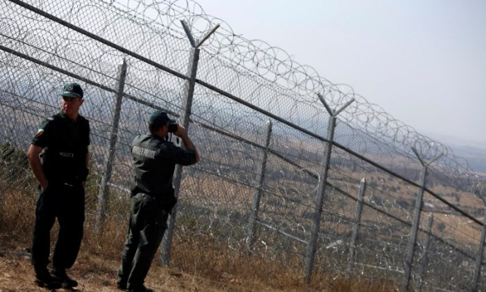 Bulgarian border policemen stand near the barbed wire fence constructed on the Bulgarian-Turkish border, near Lesovo, Bulgaria, on Sept. 14, 2016. (Stoyan Nenov/Reuters)
