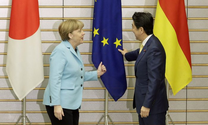 German Chancellor Angela Merkel and Japanese Prime Minister Shinzo Abe (R) talk about an EU flag at the start of talks at the latter's official residence in Tokyo on March 9, 2015. Merkel is on a two-day visit to Japan. (Kimimasa Mayama/AFP/Getty Images)