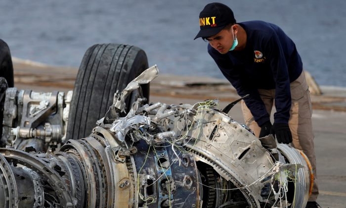 An Indonesian National Transportation Safety Commission (KNKT) official examines a turbine engine from the Lion Air flight JT610 at Tanjung Priok port in Jakarta, Indonesia, on Nov. 4, 2018. (Beawiharta/Reuters)