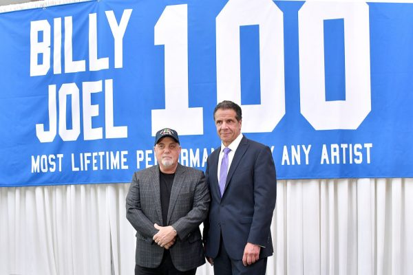 Billy Joel and New York Governor Andrew Cuomo in front of a banner