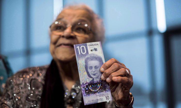 Wanda Robson, sister of Viola Desmond, holds the new $10 bank note featuring Desmond during a press conference in Halifax, on March 8, 2018. (Darren Calabrese/The Canadian Press)