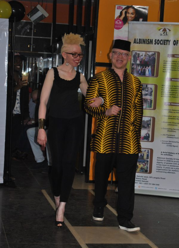 Sen. Isaac Mwaura escorts a contestant for Mr. & Ms. Albinism East Africa