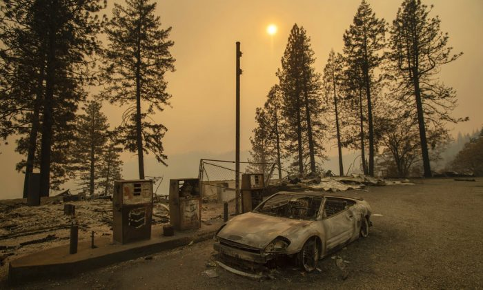 As the Camp Fire burns nearby, a scorched car rests by gas pumps near Pulga, Calif., on, Nov. 11, 2018. (AP/Noah Berger)