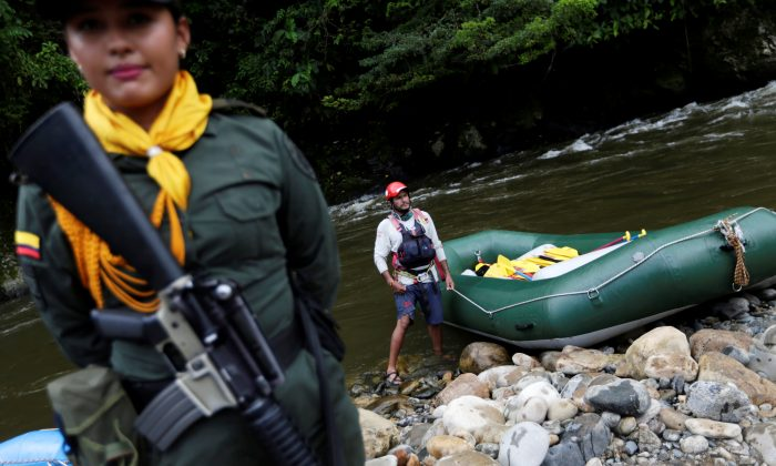 A police woman escorts an inflatable raft in Miravalle, Colombia on Nov. 9, 2018. (Luisa Gonzalez/Reuters)