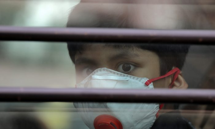 A schoolboy wearing a protective mask looks on from the inside of a school bus at Silver Line Prestige School in Ghaziabad, on the outskirts of Delhi, India, on Nov. 1, 2018.  (Anushree Fadnavis/Reuters)