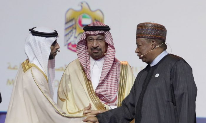 The UAE Energy Minister Suhail Mohammed Faraj al-Mazroui (L) shakes hands with OPEC Secretary General Mohammed Barkindo (R) watched by Saudi Energy Minister Khalid al-Falih (C) during the Abu Dhabi International Petroleum Exhibition and Conference (ADIPEC) in the Emirati capital Abu Dhabi, on Nov. 12, 2018.(KARIM SAHIB/AFP/Getty Images)