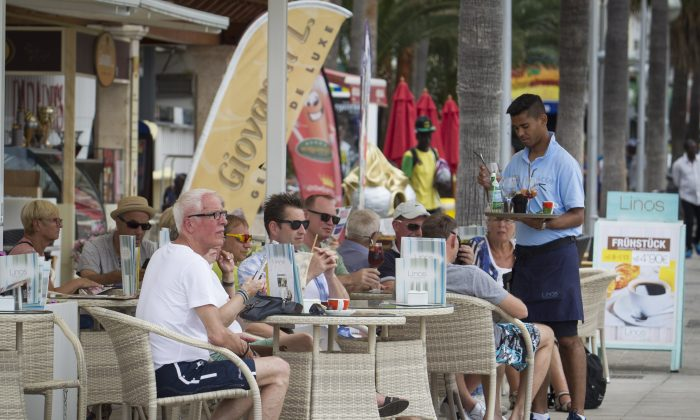 A waiter serves tourists sitting at a restaurant along Palma's Beach on Palma de Mallorca, Spain, in this file photo. (Jaime Reina/AFP/Getty Images)
