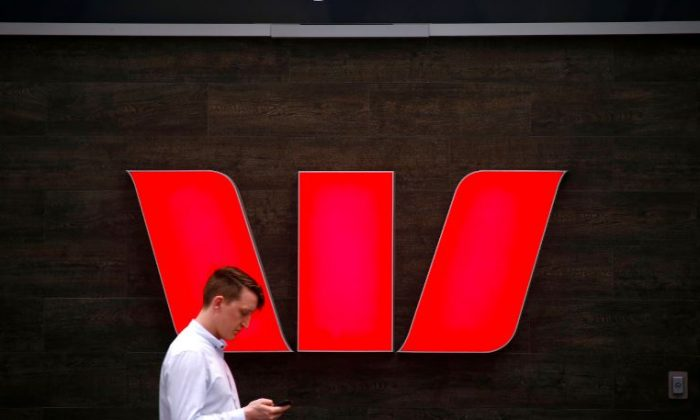 A pedestrian looks at his phone as he walks past a logo for Australia's Westpac Banking Corp located outside a branch in central Sydney, Australia, Nov. 5, 2018. (Reuters/David Gray)