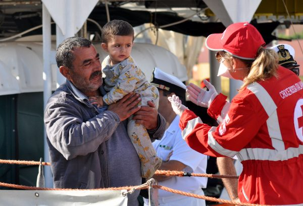 A member of the Red Cross welcomes a man holding a child