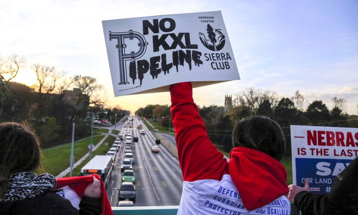 Opponents of the Keystone XL pipeline demonstrate on a pedestrian bridge during rush hour in Omaha, Nebraska, on Nov. 1, 2017. A US judge's decision to block construction of the pipeline is causing further delays moving the glut of oil out of Western Canada and into international markets. (The Canadian Press/AP, Nati Harnik)