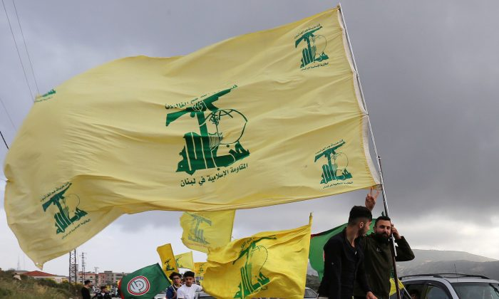 A supporter of Lebanon's Hezbollah gestures as he holds a Hezbollah flag in Marjayoun, Lebanon, on May 7, 2018. (Aziz Taher/Reuters)