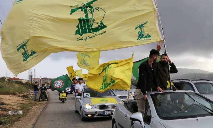 A supporter of Lebanon's Hezbollah gestures as he holds a Hezbollah flag in Marjayoun, Lebanon May 7, 2018. (Reuters/Aziz Taher)