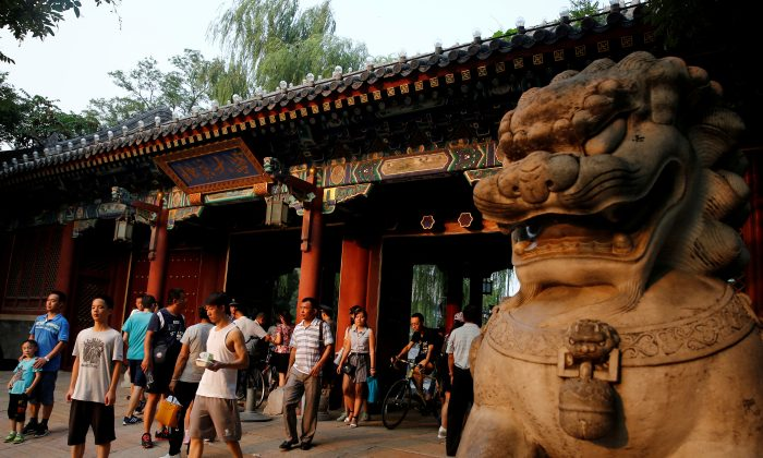 People enter and leave the gate of Peking University in Beijing on July 27, 2016. (Thomas Peter/Reuters)