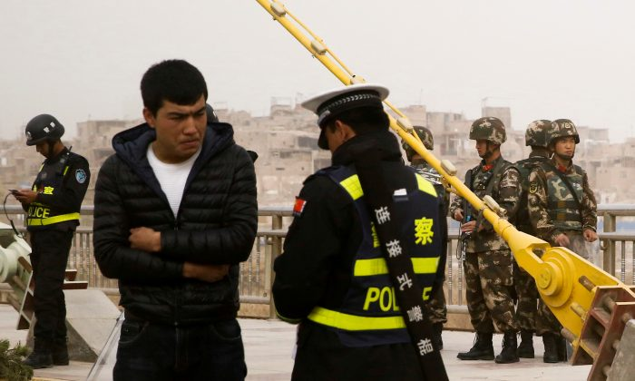 A police officer checks the identity card of a man as security forces keep watch in a street in Kashgar, Xinjiang region, China on March 24, 2017. (Thomas Peter/Reuters)