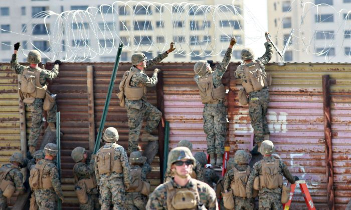 US marines put barbed wire atop feU.S. marines place barbed wire atop fencing along the United States–Mexico border in San Ysidro, Calif., on Nov. 9, 2018. (Sandy Huffaker/AFP/Getty Images)ncing along the United States-Mexico border in San Ysidro, California, on November 9, 2018. (Photo by Sandy Huffaker / AFP)        (Photo credit should read SANDY HUFFAKER/AFP/Getty Images)