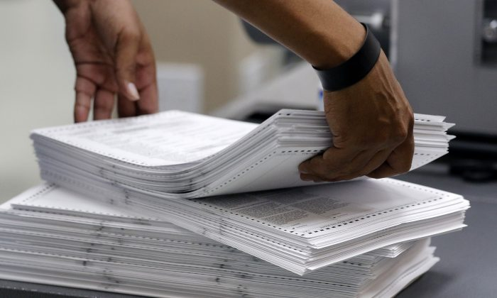 Elections staff load ballots into machine as recounting is underway at the Broward County Supervisor of Elections Office in Lauderhill, Fla., on Nov. 11, 2018. (Joe Skipper/Getty Images)