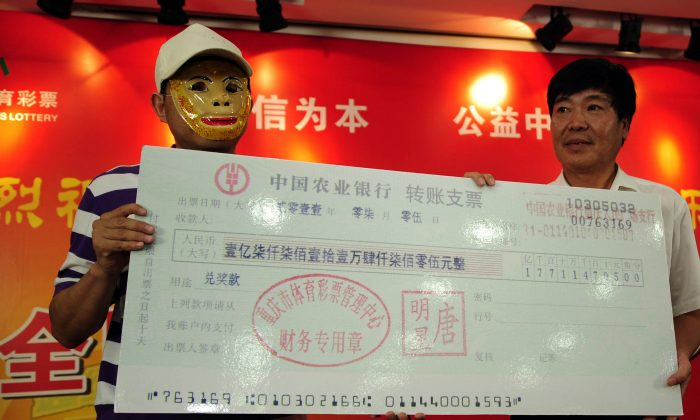 A Chinese man wears a mask to hide his identity as he recieves a mock check for 177 million yuan (26 million USD) after winning the jackpot in the China Sport lottery in Chongqing on July 5, 2011. (STR/AFP/Getty Images)