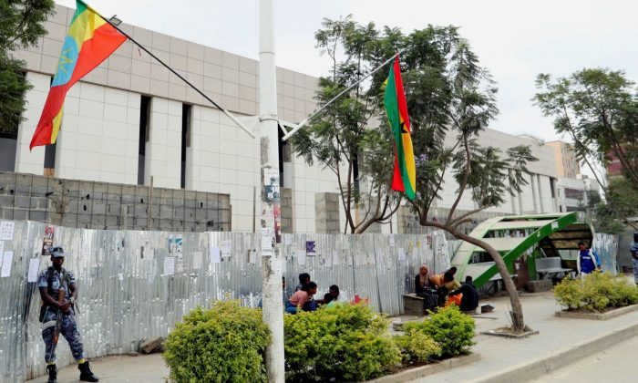 Federal police officers stand guard near Ethiopian national flags along the street in Addis Ababa, Ethiopia, on Nov. 15, 2018. (Tiksa Negeri/Reuters)