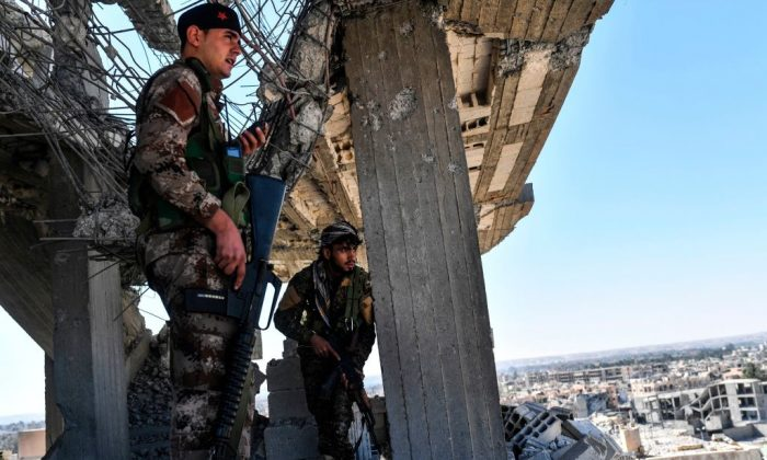 Members of the Syrian Democratic Forces, backed by U.S. special forces, walk on a building near Raqa's central hospital as they clear the last positions on the frontline on Oct. 16, 2017, in the ISIS group jihadists' crumbling stronghold. US-backed fighters have battled hundreds of ISIS jihadists holed up in the last pockets of Syria's Raqa, as the former extremist stronghold stood on the verge of capture. (Bulent Kilic/AFP/Getty Images)US-backed fighters battled hundreds of ISIS jihadists holed up in the last pockets of Syria's Raqa, as the former extremist stronghold stood on the verge of capture. (BULENT KILIC/AFP/Getty Images)