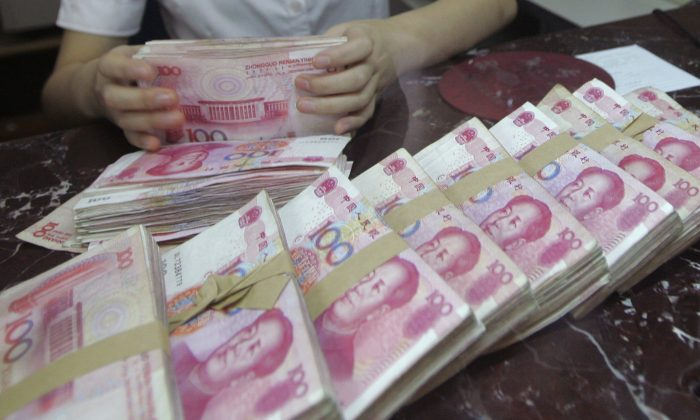 An employee counts Chinese 100 yuan banknotes at a branch of Bank of Communications in Shenyang, Liaoning Province, China on July 6, 2012. (Reuters)